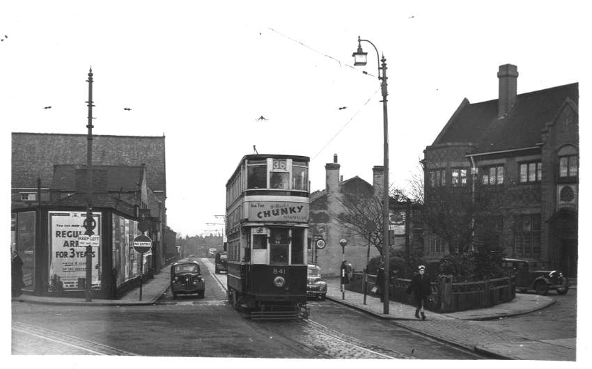 a black and white image of a double decker tram pasing a pub on the Pershore Road in Birmingham